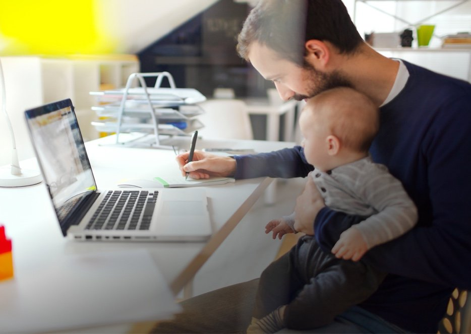 Father completing his online coursework while holding his baby.